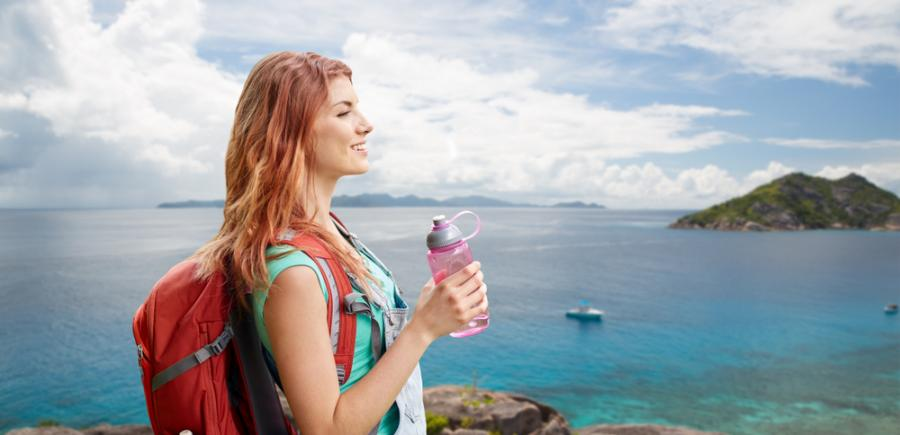 Woman hiking with a water bottle in hand