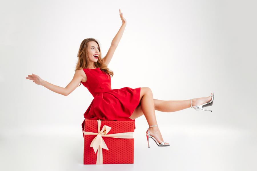 Woman wearing a red dress, sitting on top of a giant red gift box