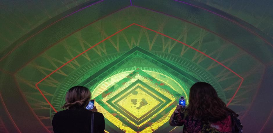 Two women taking photos of three dimensional paintings
