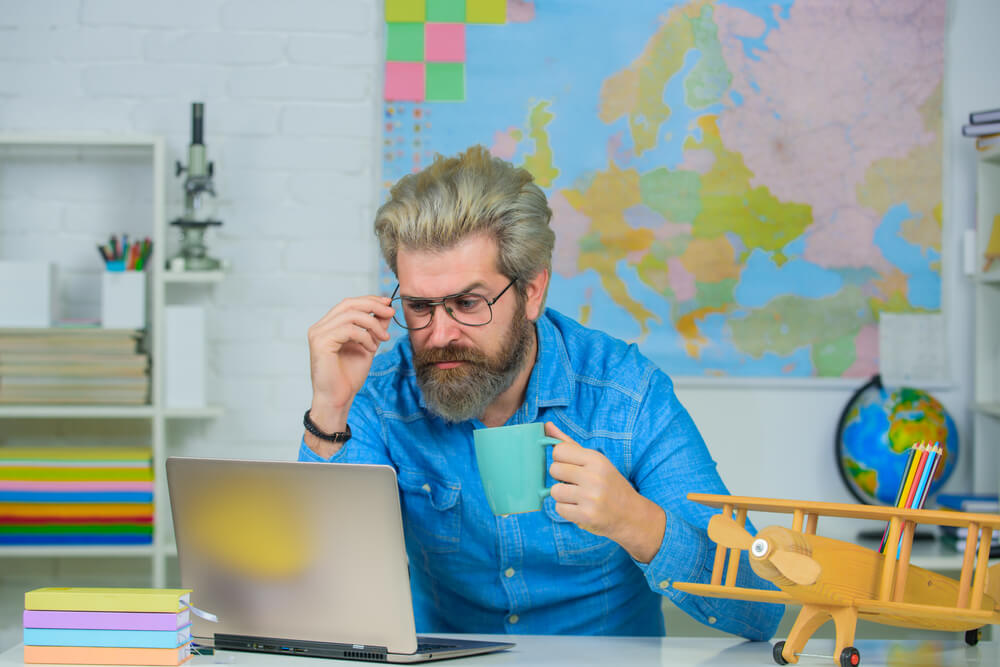 How to Write a Villain - picture of a writer at work at his laptop with a coffee mug in his hand
