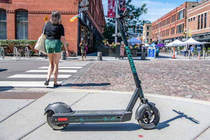 Chicago, IL - September 7. 2019: Close up of a shared scooter on a sidewalk in the West Loop, Fulton Market area, downtown Chicago. Scooter sharing is now common and popular in the city.