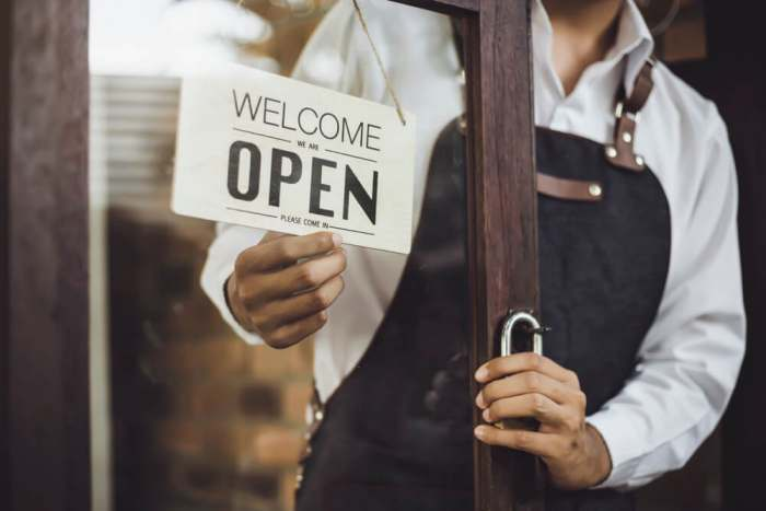uproar chicago restaurant opened Store owner turning open sign broad through the door glass and ready to service.