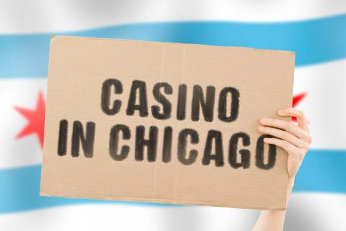 """The phrase """" Casino in Chicago """" on a banner in men's hand with blurred Dutch flag on the background. Gaming. Win. Legal business. Money. Economy. Earnings. Entertainment. Law. Legislation"""
