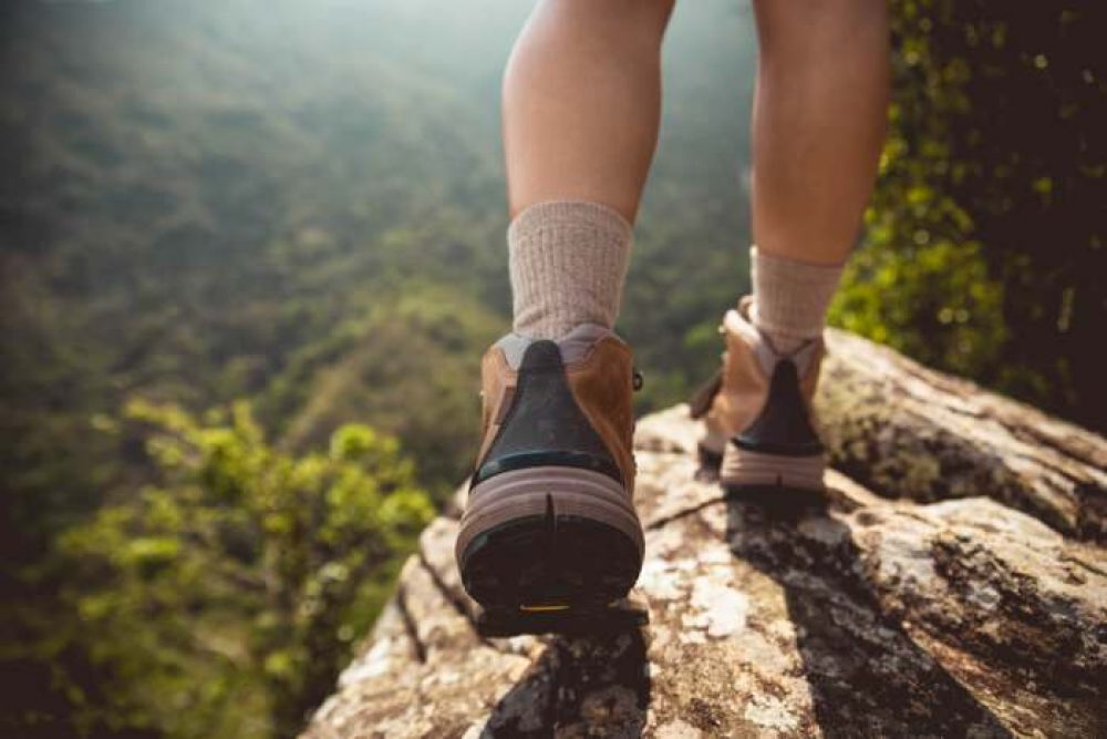 man walking in nature wearing a pair of hiking boots ands socks